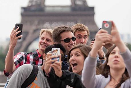 students taking selfie in front of the Eiffel Tower